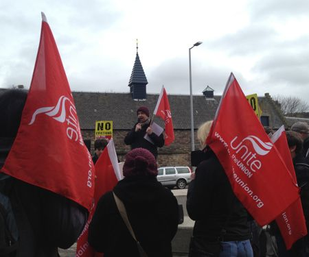speaker seen between Unite flags at bedroom tax demo