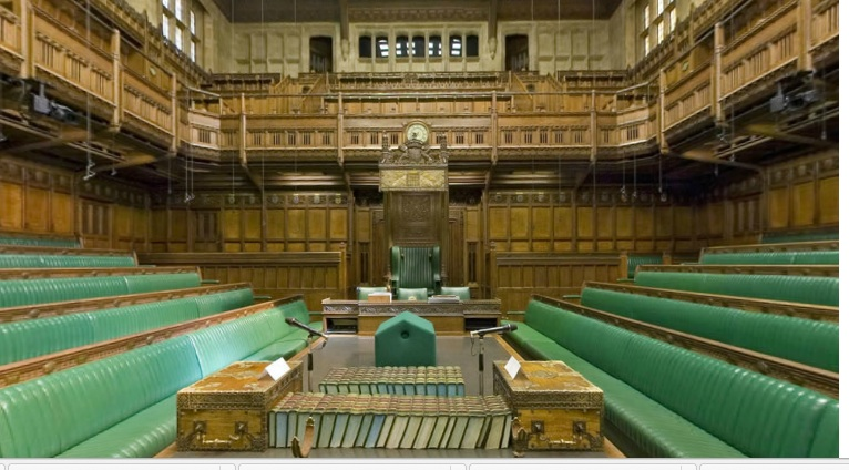 Empty green benches surrounded by handsome wood pannelling of the House of Commons