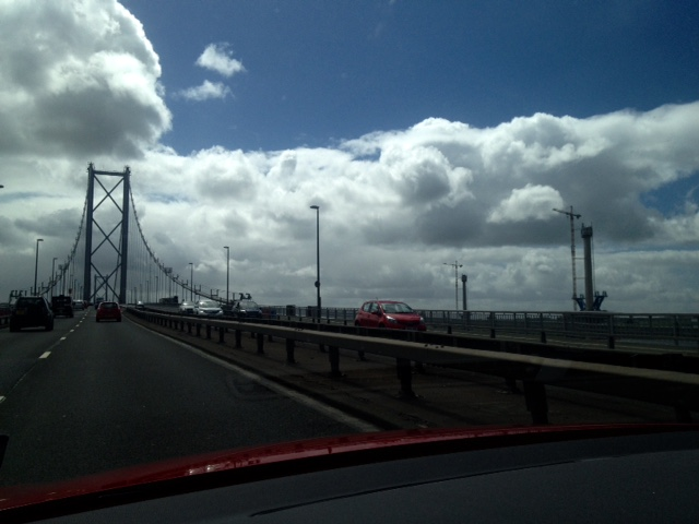 Crossing the Forth Road Bridge beneath a dramatically cloudy sky, you can just see one tower of the new bridge over to the right.