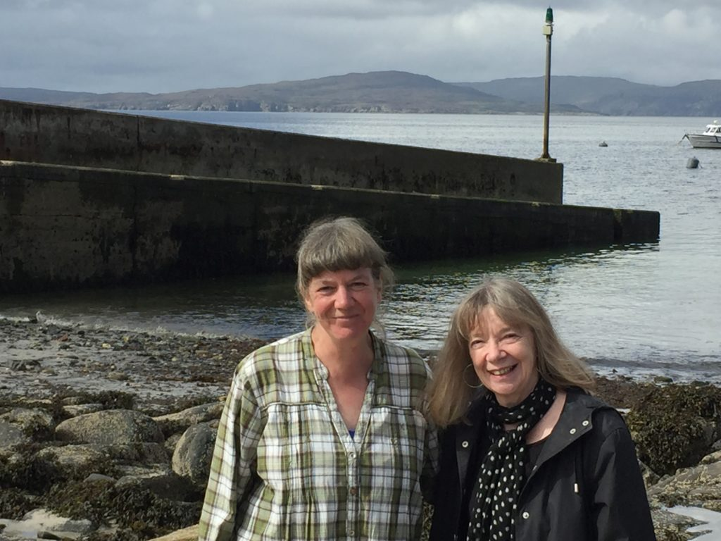 Anne Cholawo and Fay Young by Elgol jetty with Soay on the horizon