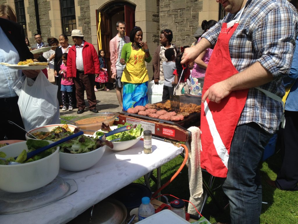A multicultural crowd queues for a barbecue in Leith, Edinburgh