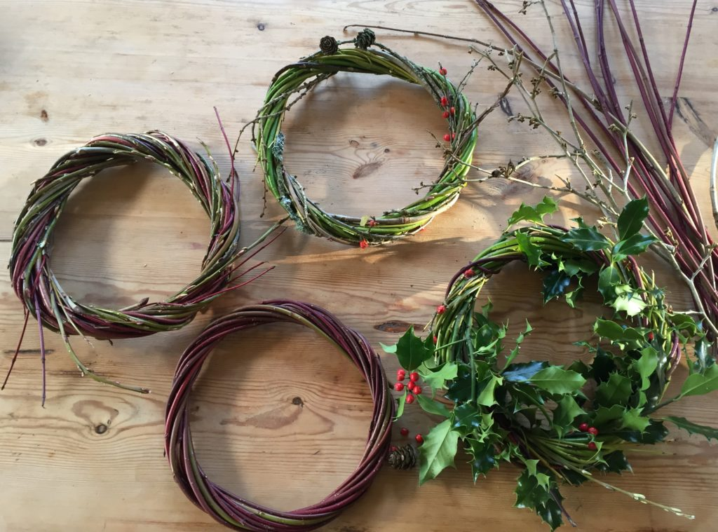 Four circles of woven stems: larch, dogwood, mixed red and green dogwood, and red-berried holly with willow